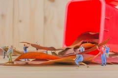het beeld van de miniarbeider van cijferpoppen verzamelt droge bladeren in Re Royalty-vrije Stock Afbeeldingen