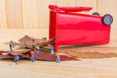 het beeld van de miniarbeider van cijferpoppen verzamelt droge bladeren in Re Stock Fotografie