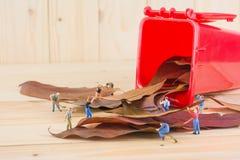het beeld van de miniarbeider van cijferpoppen verzamelt droge bladeren in Re Stock Foto's