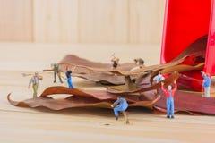 het beeld van de miniarbeider van cijferpoppen verzamelt droge bladeren in Re Royalty-vrije Stock Afbeelding