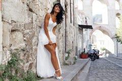 Het beeld van een schitterende donkerbruine bruid stelt sensuele dichtbijgelegen oude stad in Griekenland, de zomertijd Huwelijk  stock afbeeldingen