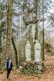 Het beeld van een vrouw die de winter dragen kleedt het bidden van vooraan een kruis in het bos royalty-vrije stock fotografie