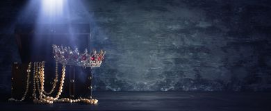 Het beeld van geheimzinnige geopende oude houten schatborst met licht en koningin/de koning bekroont met rode Robijnenstenen fant stock afbeeldingen