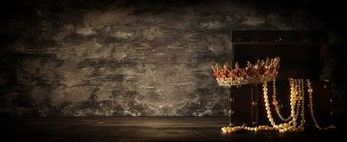 Het beeld van geheimzinnige geopende oude houten schatborst met licht en koningin/de koning bekroont met rode Robijnenstenen fant stock foto's