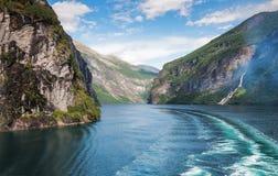 Het beeld van Geiranger-fjord, de zeven zusterswaterval en de boot slepen op het water stock fotografie