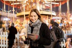 Het beeld van gelukkig brunette met glas en telefoon dient binnen avond voor gang in stock afbeeldingen