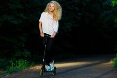 Het beeld van gemiddelde lengte van hethaired atletische vrouw schoppen op autoped in park Stock Fotografie