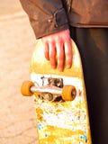 Het beeld van Grunge van een schaatser die zijn skateboard houdt Royalty-vrije Stock Foto