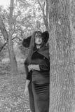 Het beeld van het mooie Meisje van Halloween in een kleding en een masker zetten zijn hand op de Zwart-witte boom Royalty-vrije Stock Foto's