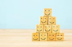 Het beeld van houten blokken met het glimlachen ziet pictogrammen over lijst onder ogen, bouwend een sterk team, personeel en beh stock fotografie