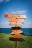 Het beeld van houten richting voorziet voor het overzees en het gras van wegwijzers stock afbeelding