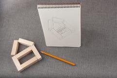 Het beeld van huis op papier, stuk speelgoed huis van houten blokken wordt gemaakt en potlood legt op grijze achtergrond die Stock Afbeelding