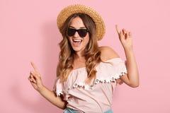 Het beeld van jong meisje met tevreden gezichtsuitdrukking die op roze achtergrond dansen, luistert aan favoriete liederen, vrouw stock fotografie