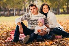 Het beeld van mooie familie in de herfstpark, jonge ouders met aardige aanbiddelijke jonge geitjes die, vrolijke persoon vijf hee Royalty-vrije Stock Afbeeldingen