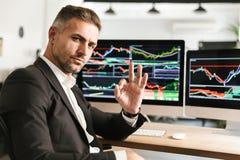 Het beeld van unshaved zakenman het werken in bureau aan computer met grafiek en grafieken bij het scherm stock afbeelding