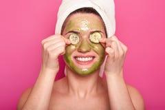 Het beeld van vrolijke jonge vrouw heeft groen masker op gezicht, toepast plakken van komkommer op ogen, gelukkig glimlacht, draa stock fotografie