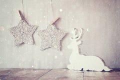 Het beeld van wit houten rendier en schittert sterren die op kabel hangen over schittert zilveren achtergrond Gefiltreerd Retro Stock Fotografie