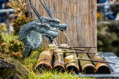 Het beeldhouwwerk van de metaaldraak met water ademhaling stock afbeelding