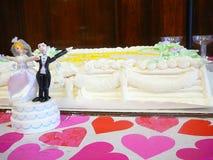 Het Beeldje van de bruid en van de Bruidegom door de Cake van het Huwelijk Stock Afbeelding