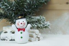 Het beeldje van de sneeuwmens op sneeuw en pijnboomboom Royalty-vrije Stock Foto