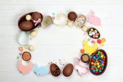 Het beeldjepaashaas van chocoladepaaseieren op een houten achtergrond stock fotografie