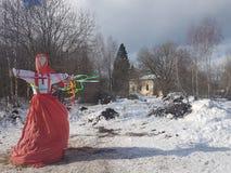Het beeltenis van Maslenitsa in Russisch volkskostuum wordt gebrand in de sneeuw tijdens de traditionele nationale feestdag van m royalty-vrije stock afbeelding