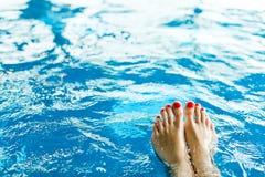 Het been van de vrouw met rode pedicure in pool - tenen stock afbeeldingen