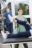 Het Beenoefening van verpleegstersassisting woman in op Rehab-Geschiktheidscentrum stock afbeeldingen