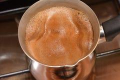 Het begin om koffie in de Turk op een plaat, de hoogste mening te koken stock afbeelding