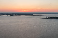 Het begin van de zon die boven de rivier toenemen De zon is in het centrum van het kader landschappen Stock Fotografie
