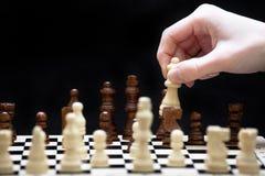 Het begin van een schaakspel en een hand Stock Foto's