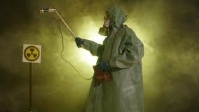 Het begrip milieuramp en stralingsverontreiniging Een man in een stralingsbeschermingspak meet straling stock video