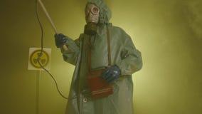 Het begrip milieuramp en stralingsverontreiniging Een man in een stralingsbeschermingspak meet straling stock videobeelden
