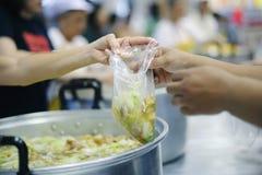 Het behandelen van de daklozen door voedsel te delen is de hoop van de armen: het concept het bedelen en honger royalty-vrije stock fotografie