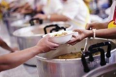 Het behandelen van de daklozen door voedsel te delen is de hoop van de armen: het concept het bedelen en honger royalty-vrije stock foto
