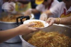 Het behandelen van de daklozen door voedsel te delen is de hoop van de armen: het concept het bedelen en honger stock fotografie
