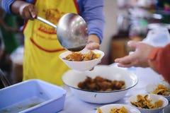 Het behandelen van de daklozen door voedsel te delen is de hoop van de armen: het concept het bedelen en honger royalty-vrije stock foto's