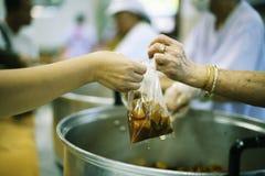 Het behandelen van de daklozen door voedsel te delen is de hoop van de armen: het concept het bedelen en honger stock afbeeldingen