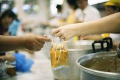 Het behandelen van de daklozen door voedsel te delen is de hoop van de armen: het concept het bedelen en honger royalty-vrije stock afbeeldingen