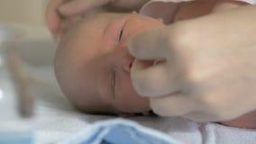Het behandelen van pasgeboren baby Moeder schoonmakende childs neus stock video