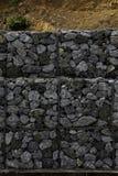 Het behouden van steenmuur naast de weg Beschermingsomheining of muur van gabions met stenen wordt gemaakt die Steenmuur met meta stock afbeelding