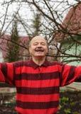 Het bejaarde begroet gasten bij zijn buitenhuis Stock Foto's
