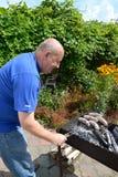 Het bejaarde bereidt worsten voor een grill op een koperslager Een picknick in het land Stock Afbeeldingen