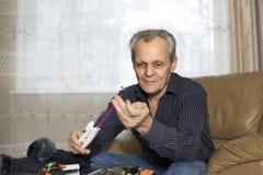 Het bejaarde controleert hengels alvorens te vissen Stock Foto's