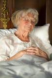 Het bejaarde dame sluimeren in haar bed stock afbeelding