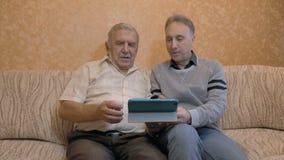 Het bejaarde en zijn volwassen zoon, bekijken de tablet De zoon onderwijst zijn vader om moderne technologie te gebruiken stock video