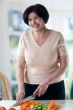 Het bejaarde gelukkige vrouw koken Stock Afbeeldingen