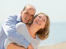 Het bejaarde het glimlachen paar koesteren Stock Foto's