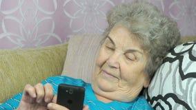 Het bejaarde houdt binnen een mobiele telefoon stock video