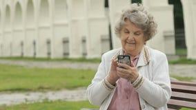 Het bejaarde houdt in openlucht zilveren mobiele telefoon stock video
